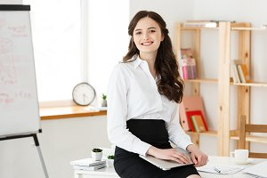 Young pretty business woman with notebook and document in the bright modern office indoors