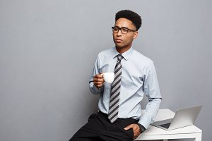 Business Concept - portrait of african american businessman having coffee sitting at a desk using a laptop.