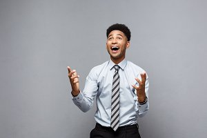 Business Concept - Confident cheerful young African American showing hands in front of him with surprising expression over grey background.