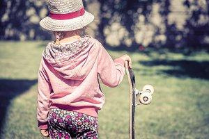 little girl is holding a skateboard