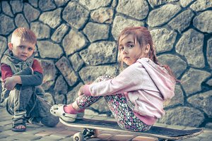 little girl and boy playing on skate