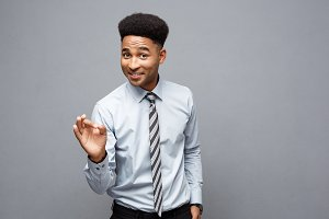 Business Concept - Confident cheerful young African American showing ok finger in front of him with surprising expression over grey background.