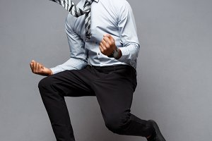 Business Concept - Full length portrait of successful african american businessman happy jumping in the office.