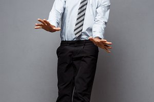 Business Concept - Full length portrait of successful african american businessman surprising jump in the office.