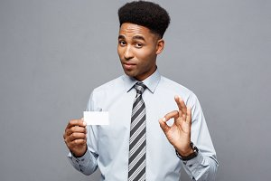 Business Concept - Happy handsome professional african american businessman showing name card to client.