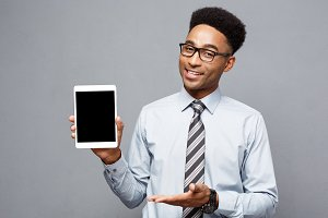 Business Concept - Happy handsome professional african american businessman showing digital tablet to client.