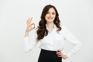 Modern beautiful business woman showing ok sign over gray background.