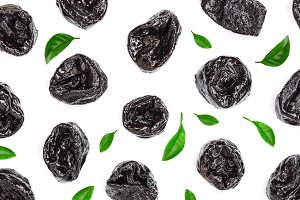 Dried plum - prunes decorated with green leaves isolated on a white background. Top view. Flat lay