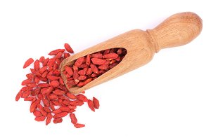 Dried goji berries in wooden scoop Isolated on white background