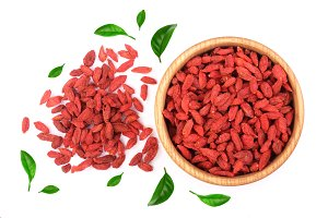 Dried goji berries in wooden bowl decorated with green leaves Isolated on white background