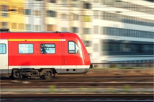 High speed red train in motion at sunset