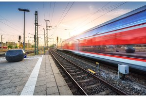 Red high speed train in motion on the railway station