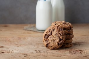 A stack of cookies with milk chocolate and two bottles of milk on a wooden table