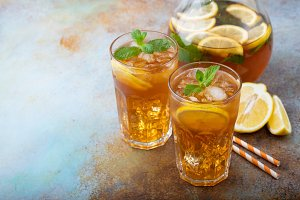 Traditional iced tea with lemon, mint and ice in tall glasses. Two glasses with cool summer drink on old rusty background. With copy space
