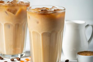 Ice coffee in a tall glass with cream poured over and coffee beans. Cold summer drink on a light blue background