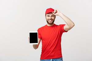 Online shopping, delivery, technology and lifestyle concept - smiling delivery man presenting tablet in his hand showing something. Isolated over white studio background.