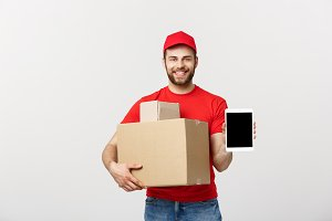 Online shopping, delivery, technology and lifestyle concept - smiling delivery man presenting tablet and holding boxes in his hand. Isolated over white studio background.