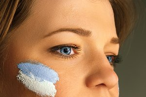 Portrait of a woman with the flag of the Argentina painted on her face.