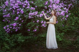Young woman near a lilac bush.