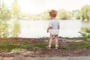 little girl walking and playing outside near lake