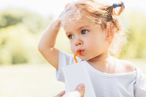 Sunny portrait of a little child drinking from a straw juiceon blurred summer background