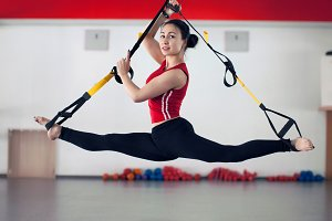 Fit pretty young woman doing fly yoga stretching exercises with trx fitness straps in fitness training white gym loft classroom.
