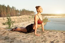 Young woman in red sport top practicing yoga in beautiful nature. Meditation in morning sunny day by Andrii Afanasiev in Sports