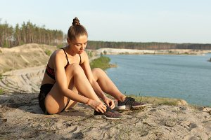 Female lacing sport shoes. Fitness woman tying shoe lace before running outdoors, workout wellness concept.