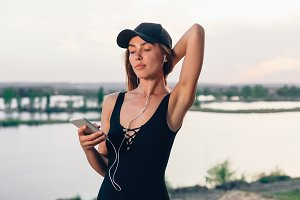 Wireless earbuds running woman on fitness workout. Active lifestyle athlete listening to smartphone music phone app with in-ear gear on beach.