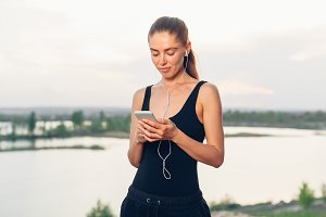 fitness girl with a smartphone on nature background, enjoys sports training, workout