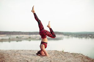 An attractive young woman doing a yoga pose for balance and stretching near the lake high in the mountains