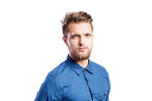 Hipster man in blue long-sleeved shirt, studio shot, isolated