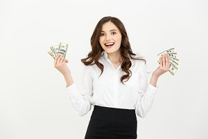 Portrait of a cheerful young business woman holding money banknotes and celebrating isolated over white background.
