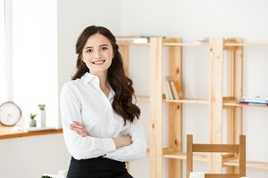 Smiling mature professional businesswoman with arms crossed sitting on the desk in office.