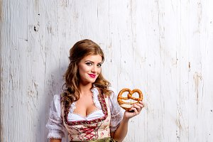 Woman in traditional bavarian dress holding pretzel, wooden back