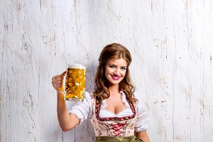 Woman in traditional bavarian dress holding beer