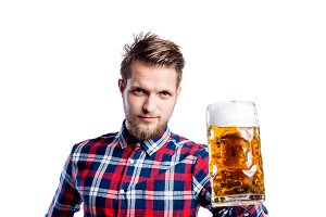 Hipster man in checked shirt holding beer, studio shot