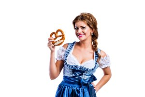 Beautiful woman in traditional bavarian dress holding a pretzel