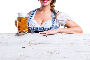 Woman in traditional bavarian dress holding mug of beer