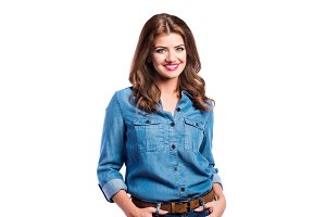 Woman in blue denim shirt and jeans, studio shot