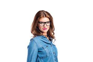 Woman in denim shirt and black eyeglasses, studio shot.