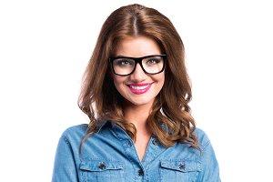 Woman in denim shirt and black eyeglasses, studio shot