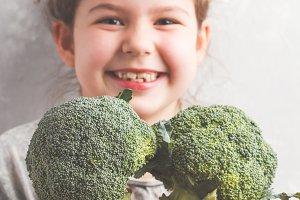 Little girl eating broccoli