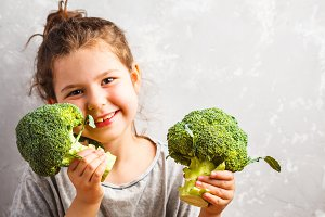 Child girl eating broccoli