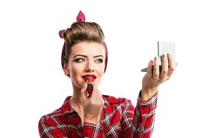 Woman with pin-up hairstyle holding mirror, applying red lipstic