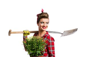 Woman with pin-up hairstyle holding yellow daisies and spade