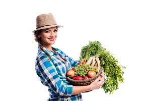Woman, checked shirt holding basket with fruit and vegetables