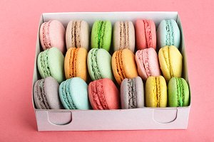 colorful macaroons in box on red white background closeup