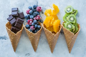 Healthy diet concept - fruits and frozen berries in ice cream cones on rustic background