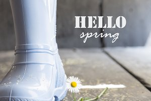 hello spring, daisy and boots on a vintage table,